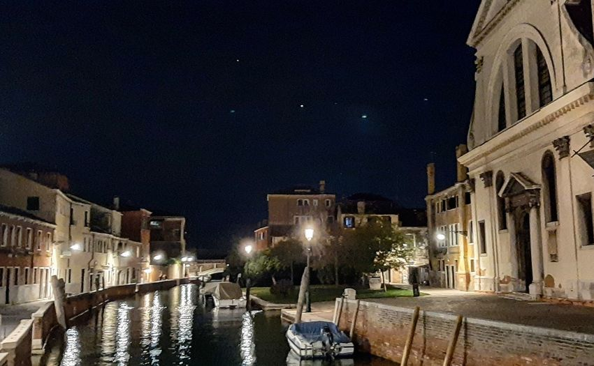 Canal passing through city buildings at night