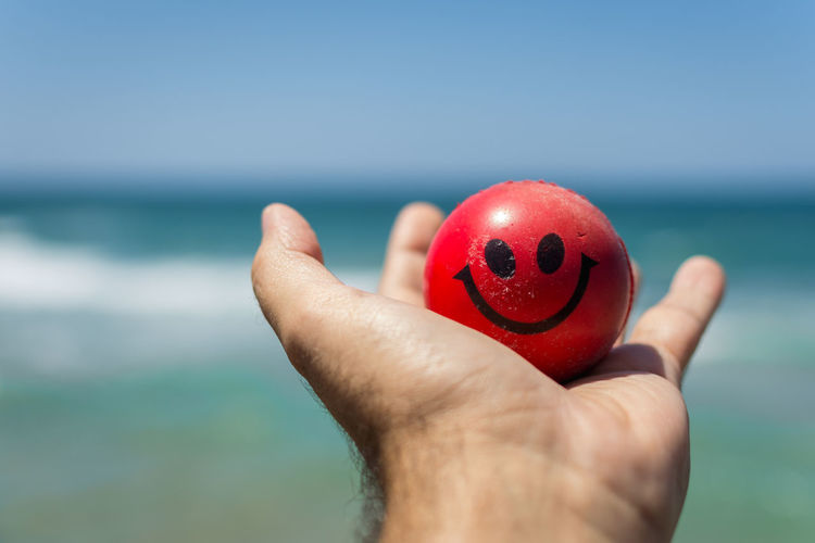 Close-Up Of Hand Holding Red Ball Against Sea