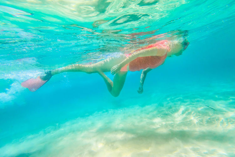 Low angle view of young woman swimming in sea