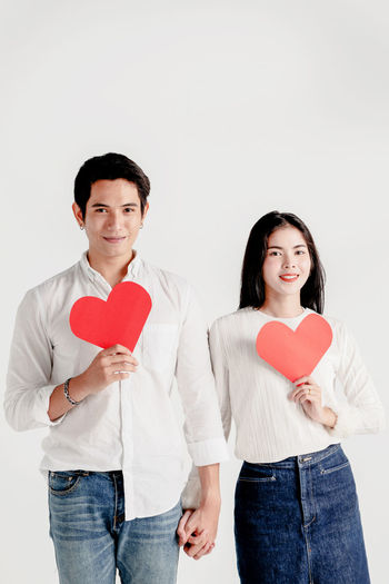 Happy young couple is holding red paper hearts Love Heart Shape Valentine's Day  Paper Emotion Cute Happiness Hug Togetherness Wedding Couple Couple - Relationship Romantic Males  Females Women Man Surprise Married Present Lifestyles Leisure Activity Relaxing Anniversary New Year