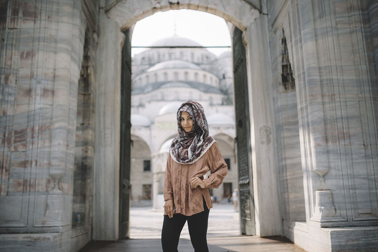 Portrait of confident woman with hand on hip wearing hijab while standing against built structure