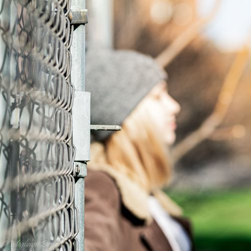 Close-up of person standing on metal fence