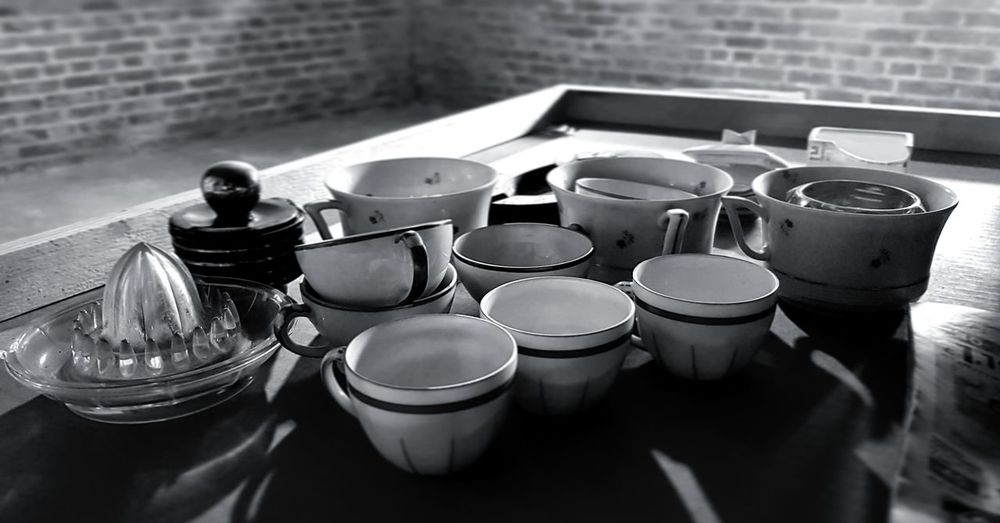 High angle view of cups and juicer on table