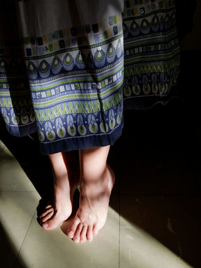 Low section of woman tiptoeing on tiled floor at home