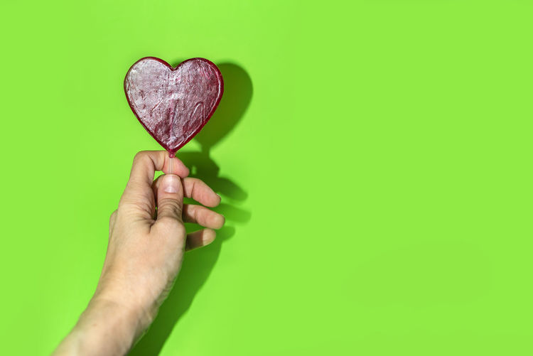 Hand holding a red heart lollipop on green background with copy space. Love concept. Indoors  No People Studio Shot Backgrounds Copy Space Wallpapaer Heart Shape Lollipop Red In Love Romance Romantic Celebrate Celebration Object Colorful Fun Tasty Delicious Hand Holding People person Green