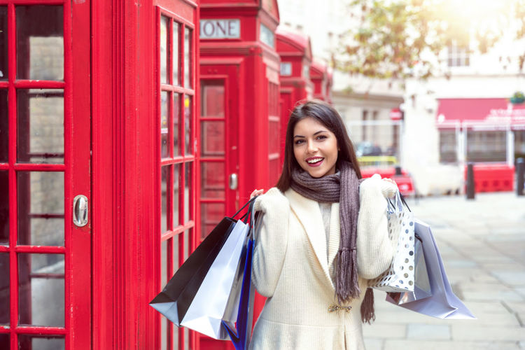 Young woman with shopping bags in her hand in front of red telephone booths in London, UK Smiling Young Adult Red One Person Happiness Portrait Young Women Lifestyles Bag City Consumerism Standing Beauty Casual Clothing Leisure Activity Beautiful Woman Looking At Camera London Shopping Bags Telephone Booth United Kingdom Day Concept Travel