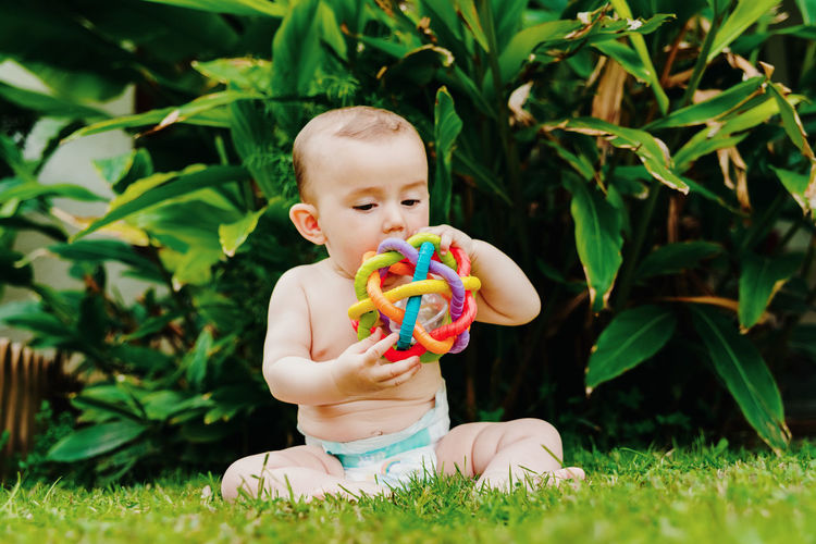 Cute baby girl playing with toy on field