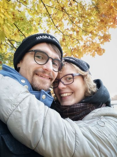 Portrait of couple smiling while standing against autumn tree