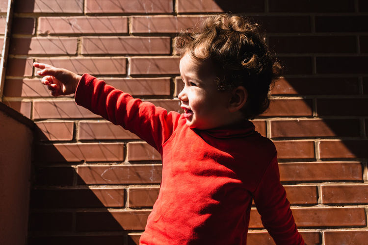 Side view of boy against wall