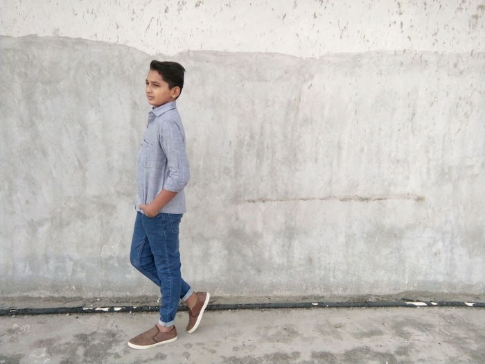 Teenage Boy Standing Against Concrete Wall