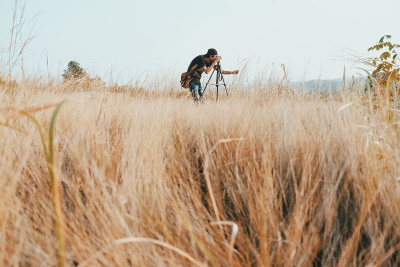 Side view of man photographing on grassy field