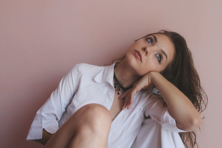 Thoughtful Young Woman Sitting Against Peach Wall