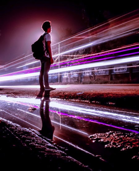 Man standing by light trails on road in city at night