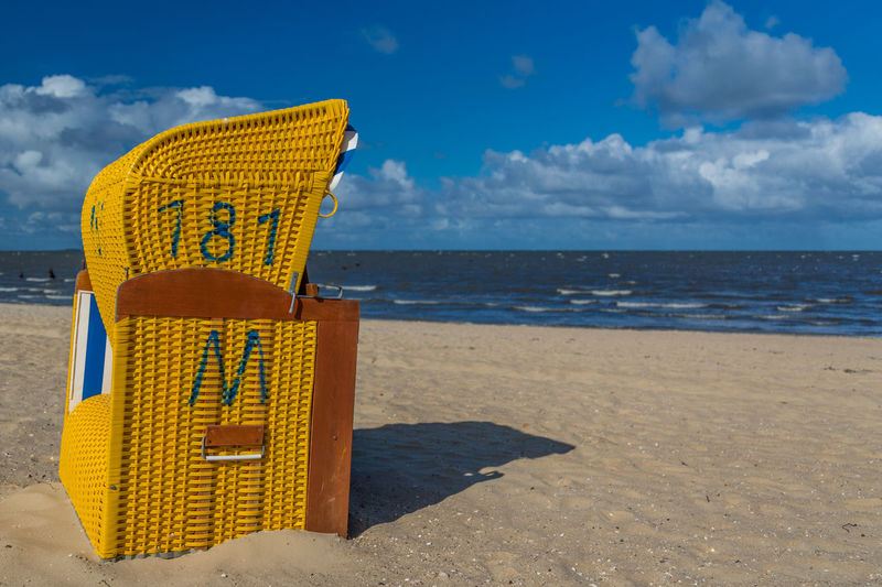 Yellow Hooded Beach Chair At Beach During Sunny Day