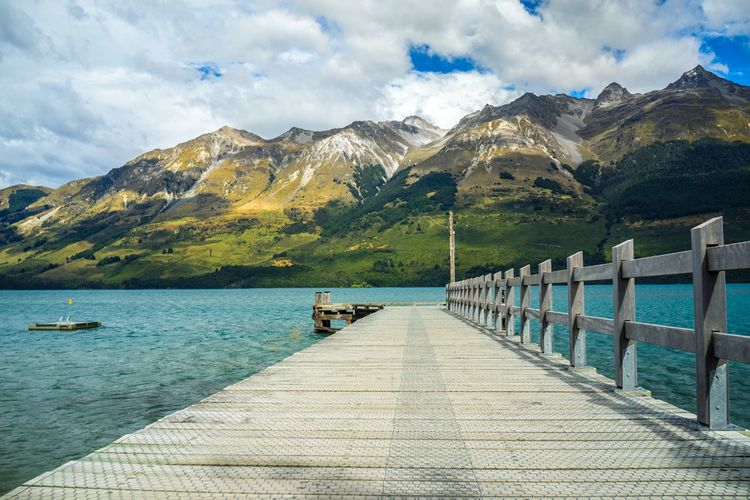 Wooden Pier At Lake Against Mountains