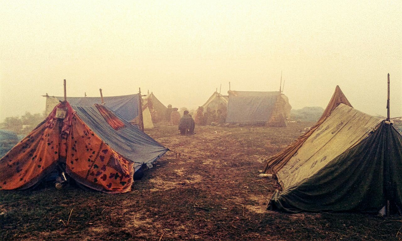 People on field by tents against clear sky during foggy weather