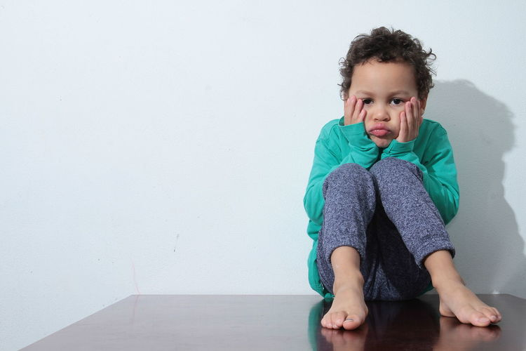 Portrait of sad boy sitting on table against wall at home
