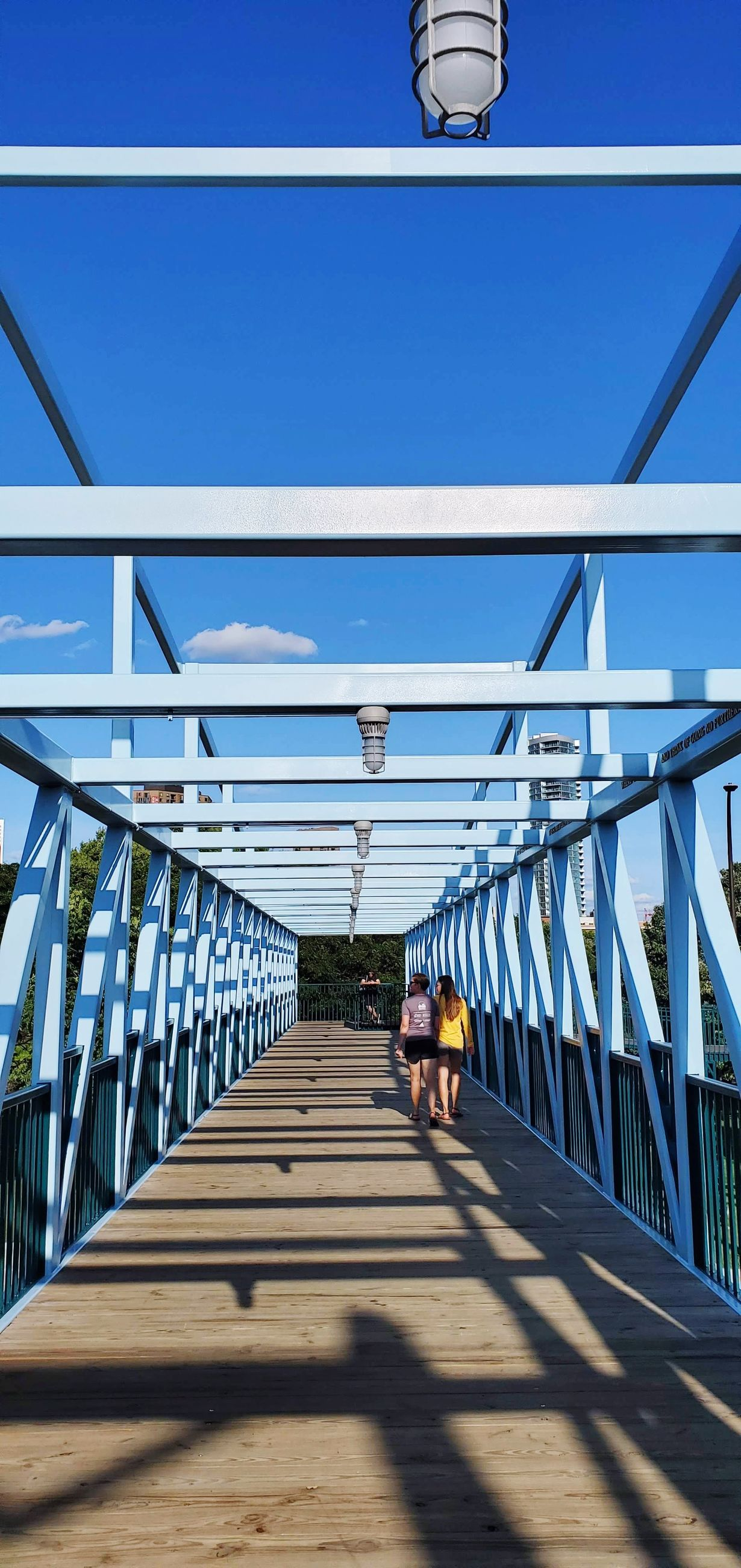 architecture, built structure, railing, sunlight, shadow, the way forward, one person, direction, real people, bridge, lifestyles, nature, sky, footbridge, day, men, bridge - man made structure, connection, full length, outdoors, diminishing perspective, ceiling