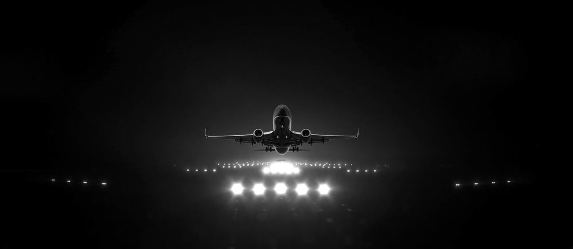 Low angle view of airplane flying in sky at night