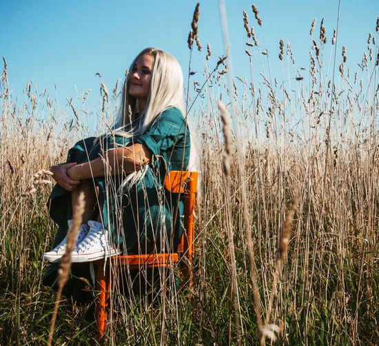 Woman sitting on field by plants against sky