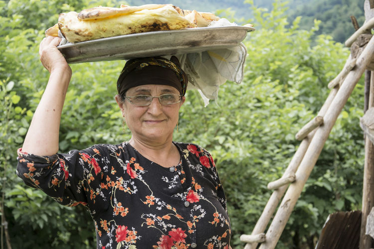 Portrait of smiling senior woman carrying food on head