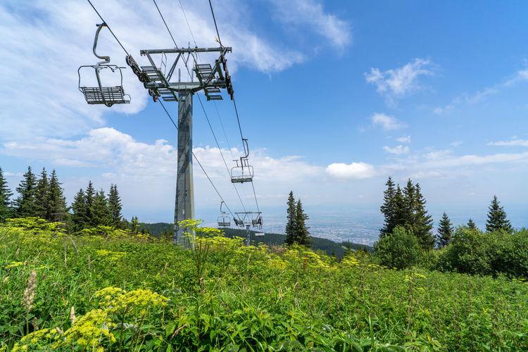 Electricity pylon on land against sky