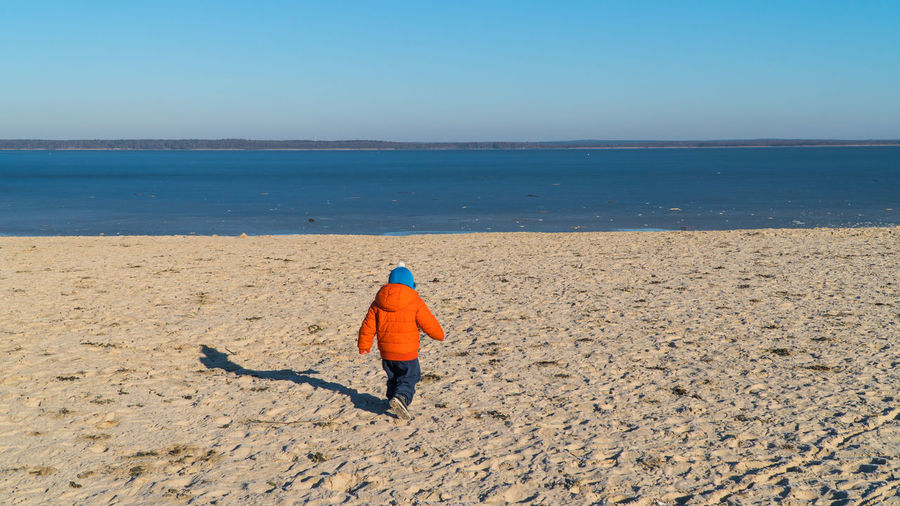 Rear view full length of boy walking at beach