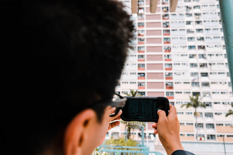 Close-up of man photographing building with mobile phone in city