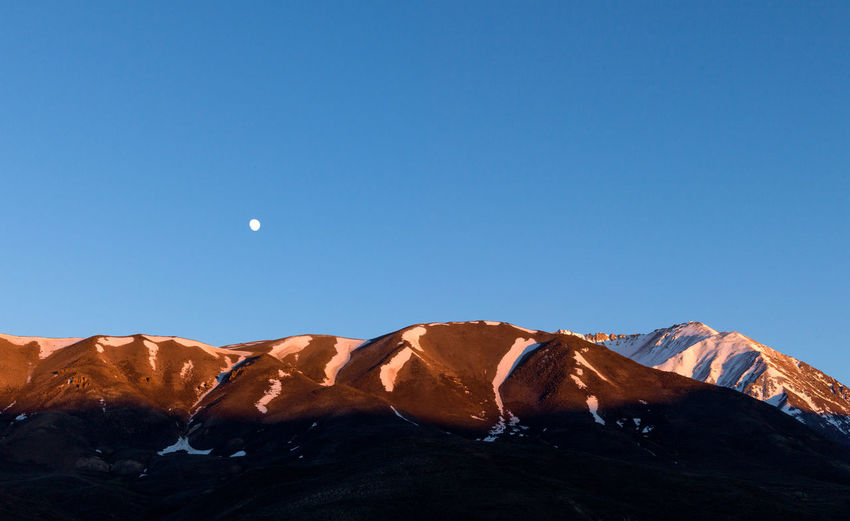 Sunset in the andes mountain range with the moon on the horizon