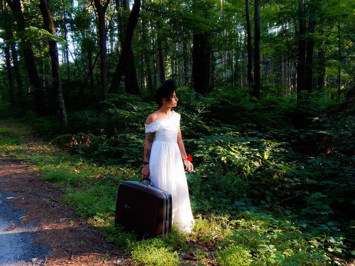 Woman Holding Luggage While Standing On Field In Forest