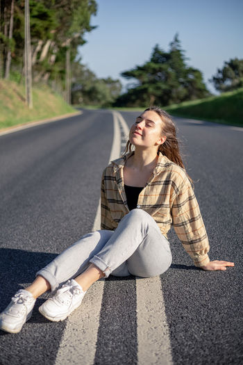 Young woman sitting on road