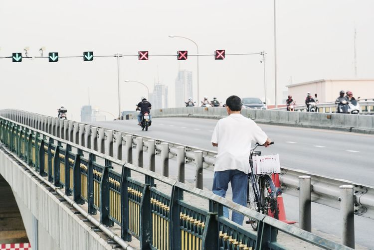 Man with bicycle on bridge against sky