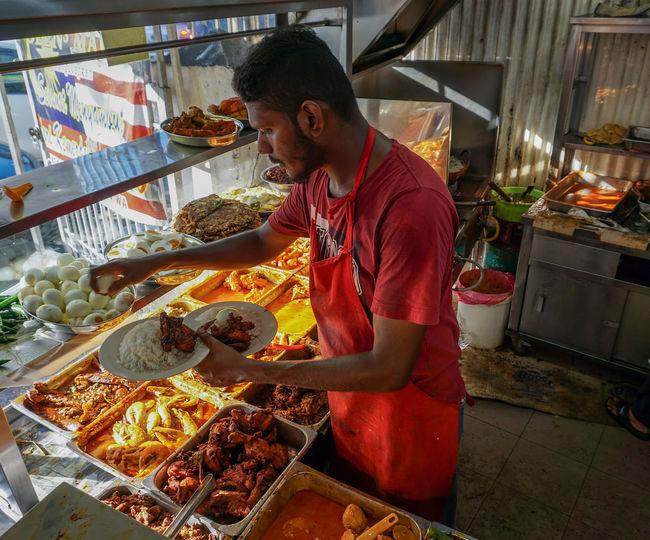 Side view of a man preparing food