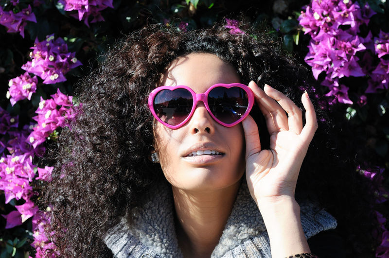 Portrait of young woman wearing sunglasses against bougainvillea
