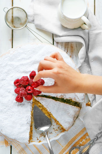 Cropped hand of woman arranging raspberries on sponge cake
