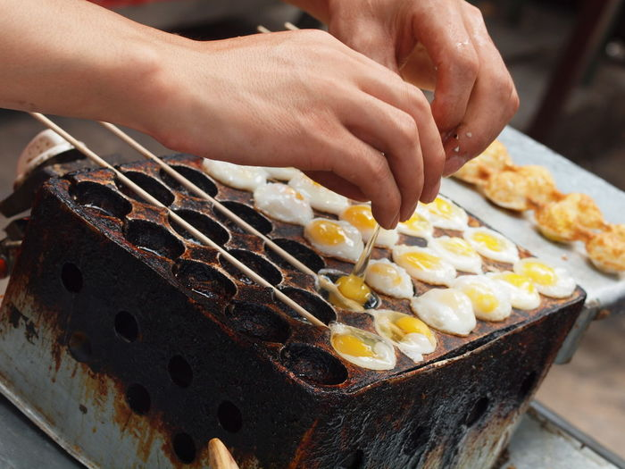 Cropped Image Of Vendor Cooking Eggs