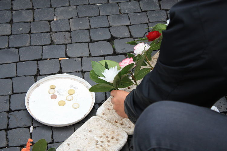 Cropped man putting artificial flower on polystyrene with coins in plate on footpath