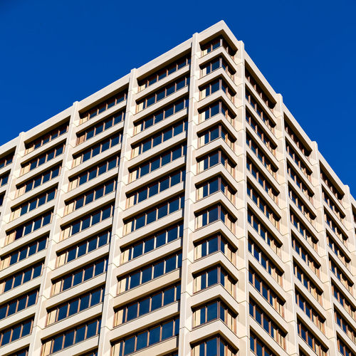 Low angle view of apartment building against clear blue sky