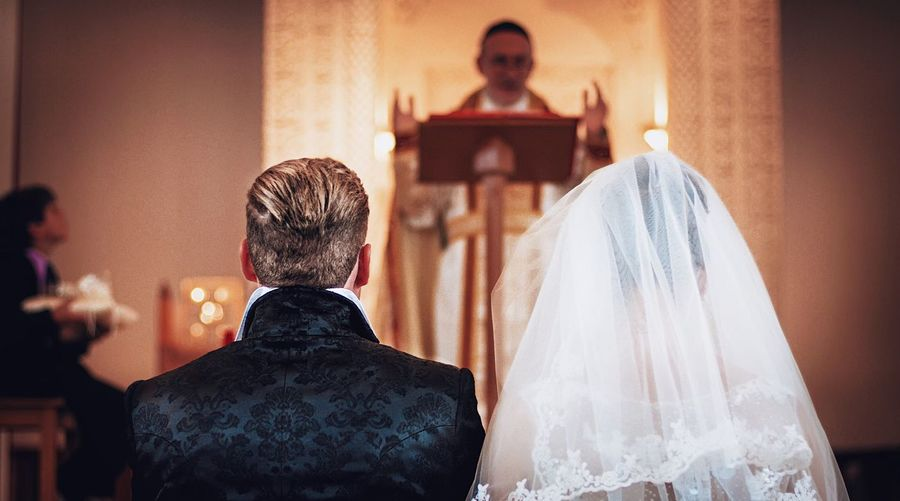 Rear view of bride and bridegroom standing at altar during wedding ceremony