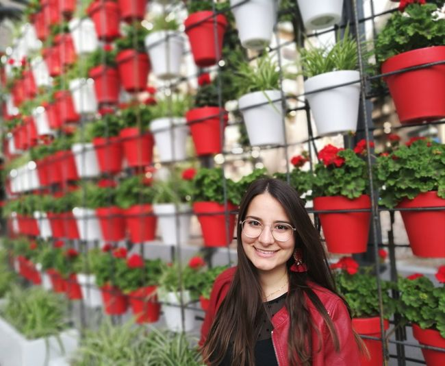 Portrait of smiling young woman against potted plants