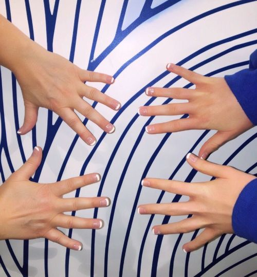 Cropped hand of mother and daughter showing nail polish on white and blue table