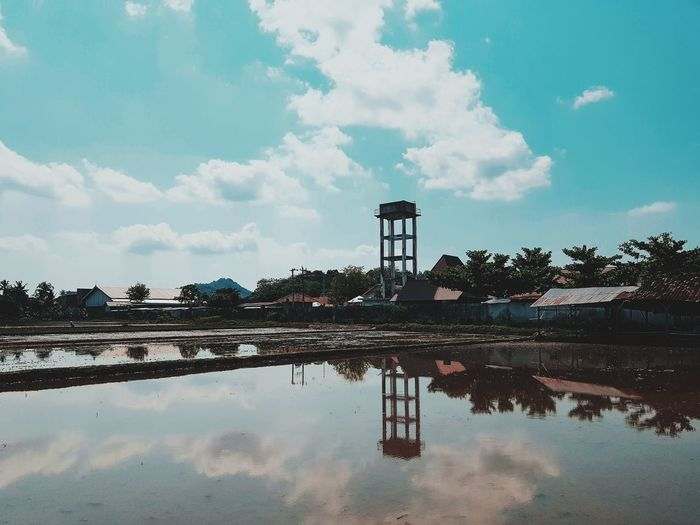 Reflection of water tower in pond against sky