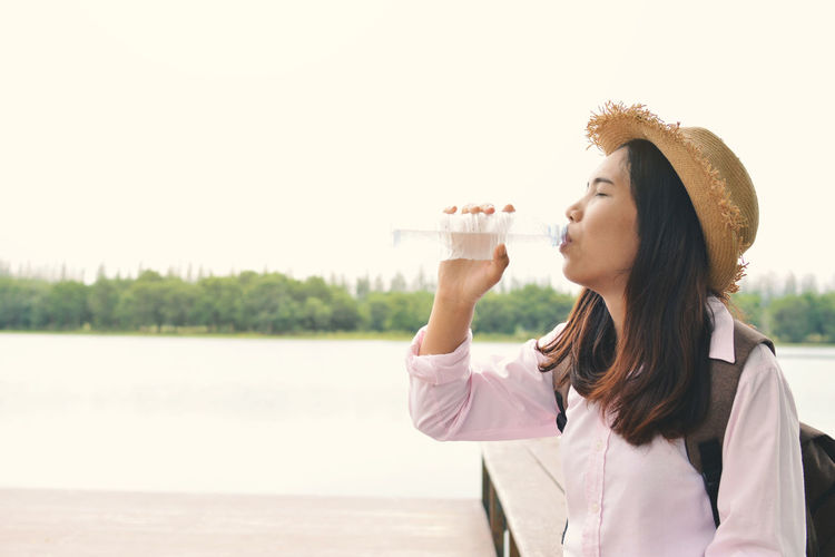 Thirsty young woman drinking water at lakeshore against clear sky