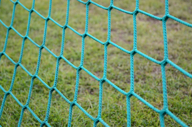 Full frame shot of soccer net against grass