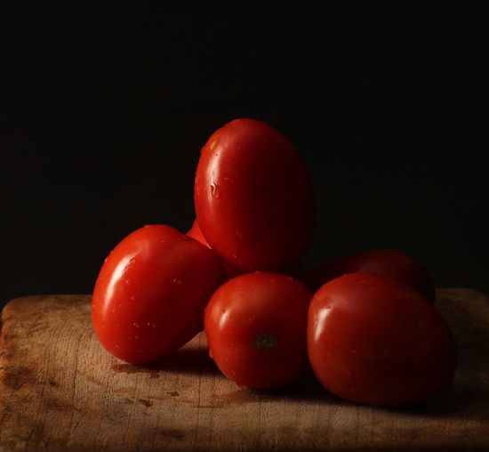 Close-up of tomatoes on table against black background
