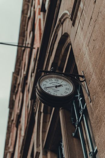 Low angle view of clock on building wall