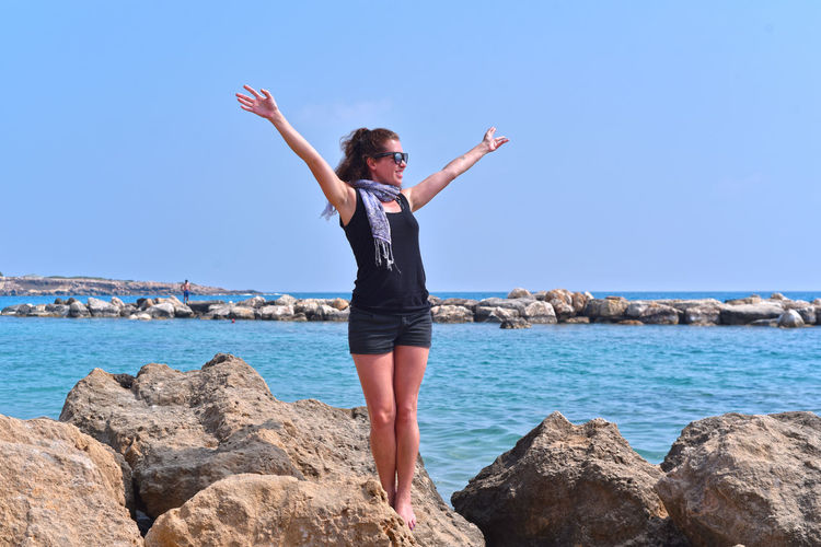 Sky One Person Water Solid Sea Rock - Object Rock Human Arm Leisure Activity Real People Young Adult Lifestyles Full Length Beauty In Nature Blue Limb Standing Arms Outstretched Arms Raised Horizon Over Water Paphos Cyprus