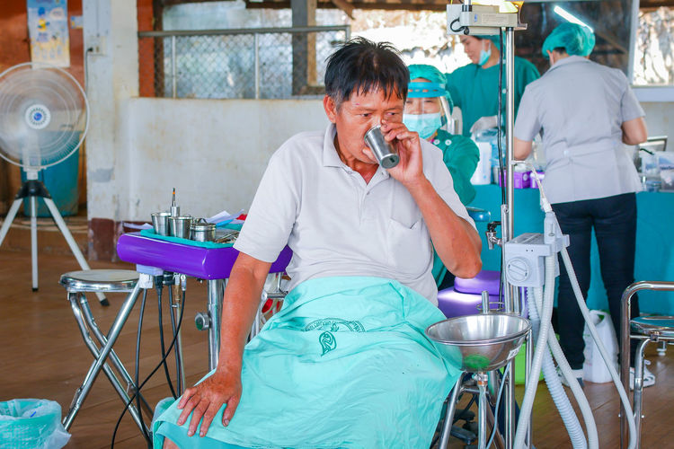 Chiang Rai, Thailand Help Thailand Hospital Dental Health Public Healthcare And Medicine Medical Volunteer Using Phone Telephone Real People Sitting Communication Women Technology People Talking Holding Front View Wireless Technology Mobile Phone Men Adult Lifestyles Indoors  Looking Chair