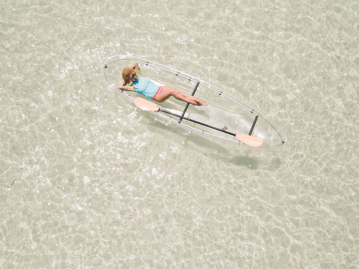 High angle view of girl relaxing in a transparent canoe in tropical waters
