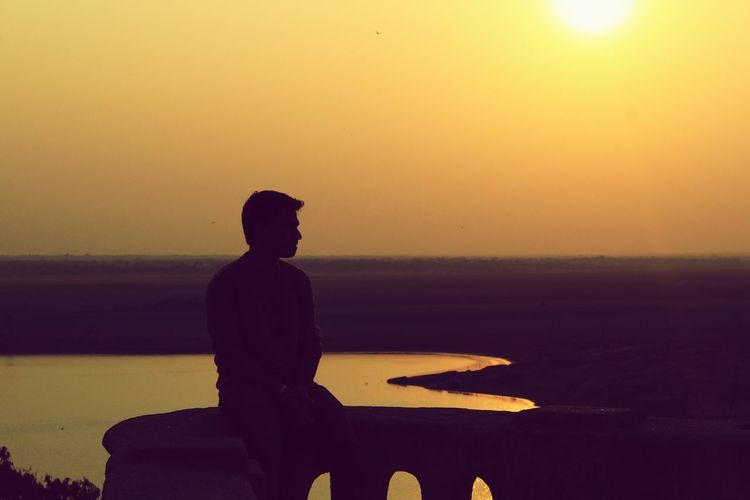 Silhouette Of Man Sitting By Sea During Sunset